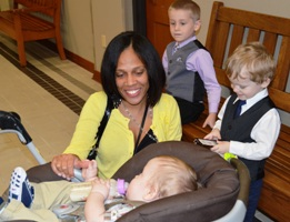 HCJFS Caseworker Leah Houchins greets Levi, 1, Westen, 3, and Aiden, 5, before their adoption Tuesday.